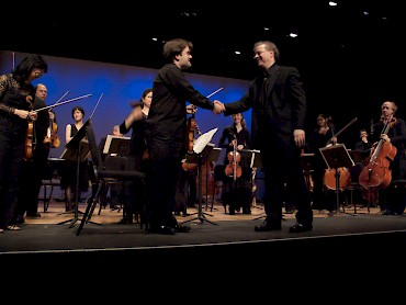 Aaron Boyd, concertmaster, Karchin, and the orchestra